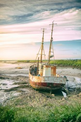 Abandoned old boat on the shores of a river