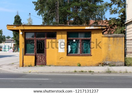 Abandoned old dilapidated yellow security guard entrance to workplace building with cracked wooden doors and facade in front of asphalt road with large trees and construction material in background stock photo