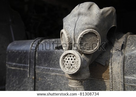 Abandoned old dirty gas helmet hanging on rusty metal gas tank as a symbol of destruction