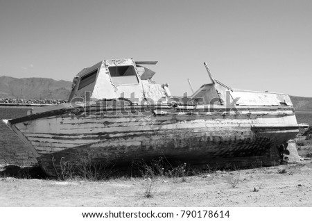 Abandoned old fishing boat on the sea shore. Black and white photography. #790178614