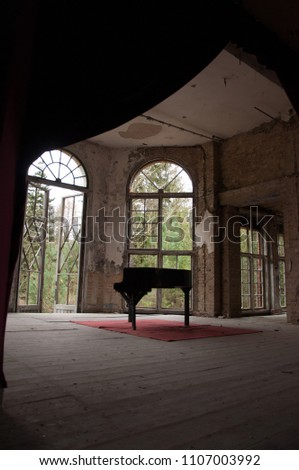 abandoned old german theater - destroyed piano on stage - scary haunted old house #1107003992