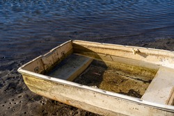 Abandoned old steel dingy boat, washed up on shoreline.