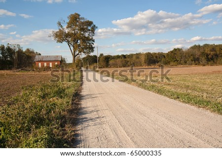 Abandoned on-room schoolhouse on a rural, gravel road in Indiana with a large tree, bright blue sky and clouds