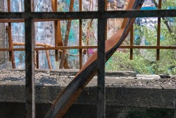 Abandoned prison building littered with graffiti and decay as nature takes over. A rusted twisted metal beam trapped between two barred windows.