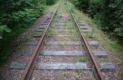 Abandoned railroad with rusty rails and rotten wooden sleepers in the woods. Concept of crisis in transportation
