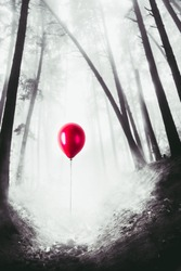 abandoned red balloon in the forest, lost children concept / selective color, high contrast image