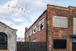 Abandoned run down industrial building broken smashed windows neglected empty damaged. Red brick building boarded up birds flying in sky behind vandalised shabby deserted derelict old house.