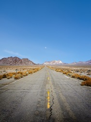Abandoned rundown road, moon and distant mountains in remote west Nevada
