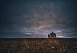 Abandoned Rural Farmhouse in a Large Field under a Dramatic Sky