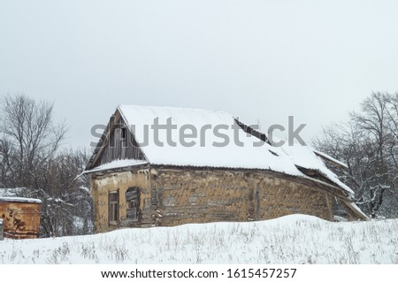 Abandoned rustic cold old house with a collapsed roof. Winter nature of secluded countryside. Russia life remote place stock photo