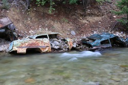 Abandoned rusting cars in river with rocks.