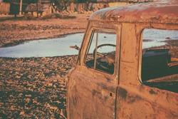 Abandoned rusty car in garden