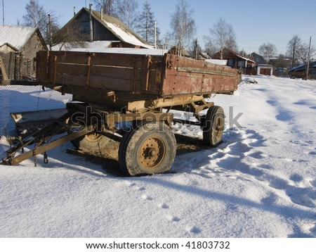 Abandoned rusty farm trailer under snow in russian village - stock photo