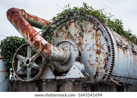 abandoned rusty machinery mixed with nature
