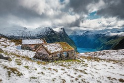 Abandoned scandinavian cabins with grass roof in snowy high mountains in Norway