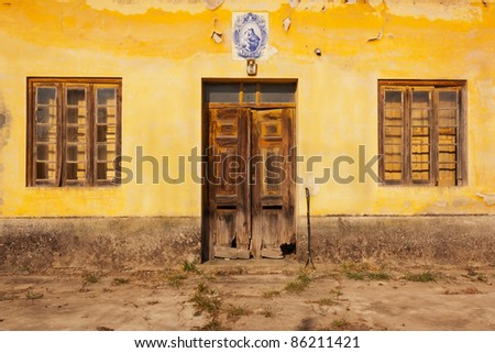 Abandoned school facade with wood windows and doors in Portugal - stock photo