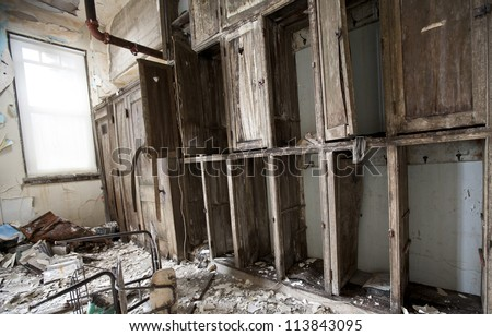 Abandoned school in Detroit Michigan. The cabinets are falling apart and papers are scattered on the floor.