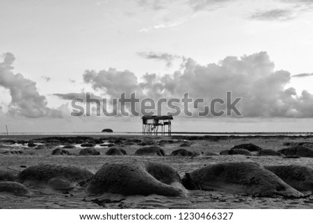 Abandoned sea house building surrounded by boulders during low tide