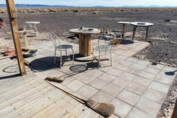 Abandoned seating area with metal chairs, a spool, and a broom, out in the desert
