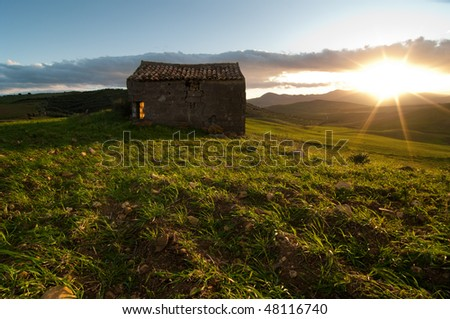 abandoned shack in a grassy field at the sunset, the backlight of sunset is filled in with light flash producing a particular brightness