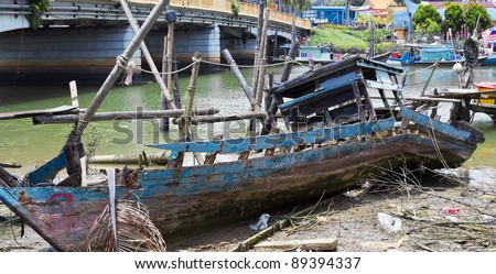 Abandoned shell of a wooden fishing boat on the banks of the Mersing River,in Mersing  Malaysia,  after all the valuable parts had been scavenged. It has been stripped down to it hull.