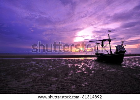 Abandoned ship at the beach with twilight sky in purple and red