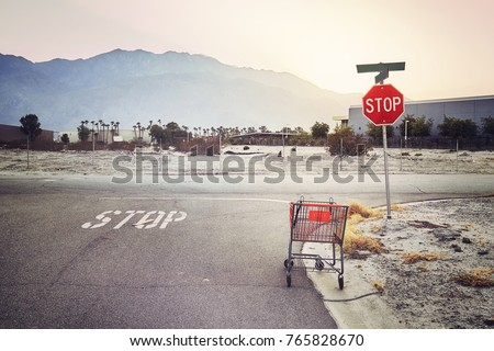 Abandoned shopping cart on a street at sunset, color toned picture, USA. #765828670
