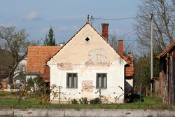 Abandoned small old red bricks suburban family house with cracked facade and two dilapidated wooden frame windows surrounded with other buildings and wooden barn