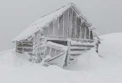 abandoned snow-covered hut (cabin) in winter