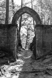 Abandoned stone gate with Gothic Arch near Mala Skala, Czech Republic Black and white image.