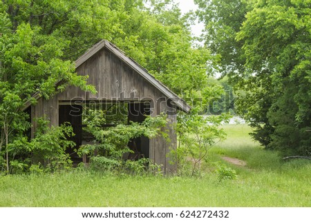 abandoned texas barn in the countryside with a little lake in the background and a bunch of trees stock photo