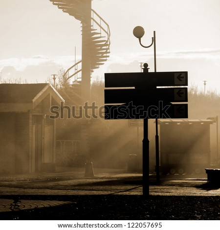 abandoned town street with mist and sunrays at the sunset