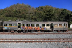 abandoned train car in a remote rural rail track with mountain and in the background. abandoned train painted by graffiti.