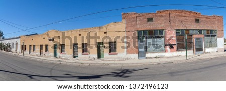 Abandoned Tucson, Arizona city block of vintage buildings under blue sky.