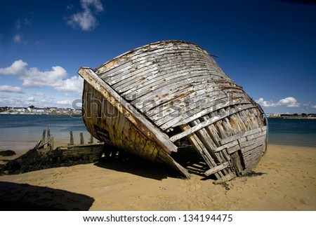 Abandoned wooden boat . Old fishing boat sun-bleached abandoned on sand. Ethel, Brittany, France - stock photo
