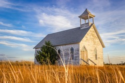 Abandoned Wooden Church Building in the Midwest Prairie under Blue Summer Sky