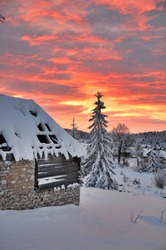 Abandoned wooden hut covered with snow.
