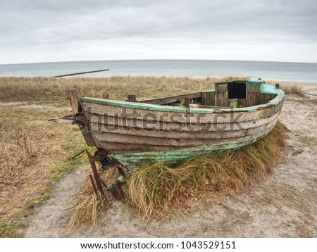 Abandoned wrecked boat stuck in sand. Old wooden boat on the sandy shore of beach. Sunset on the beach. Sparse vegetation.