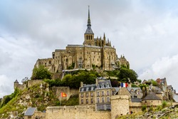 Abbey Mont Saint-Michel (7th century) at rocky tidal island in Normandy - one of most visited tourist sites in France. Mont-Saint-Michel and its bay are part of UNESCO list of World Heritage Sites.