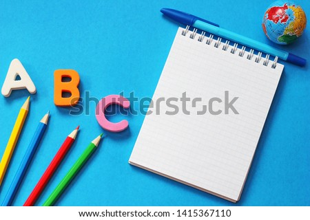 ABC-the first letters of the English alphabet on a blue background. Notebook and pen. Pencils of different colors and small globe. Empty space for text. Learn foreign languages. English for beginners