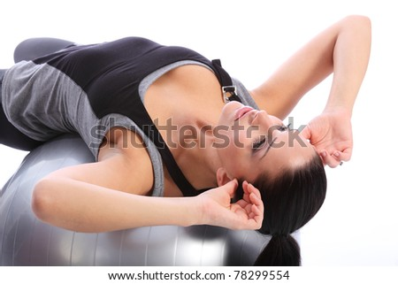 Abdominal stomach crunches exercise by beautiful young caucasian woman in gym leaning back on fitness exercise ball. She is wearing a grey and black sports outfit.