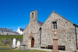 Aberdaron village, Wales. Historic church of Saint Hywyn. Beautiful old landmark which was a place to worship for pilgrims heading to Bardsey island in medieval times. Blue sky and copy space.