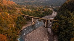 Abkhazia, old railway, arch bridge across the river, autumn forest. A blue river, a stone bridge and yellow, green trees. Top view.