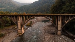 Abkhazia, old railway, arch bridge across the river, autumn forest. A blue river, a stone bridge and yellow, green trees. Side view.