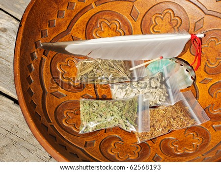 Aboriginal smudge kit with sweet grass, cedar, tobacco, sage, a feather, a shell and a match in a rustic wooden bowl.