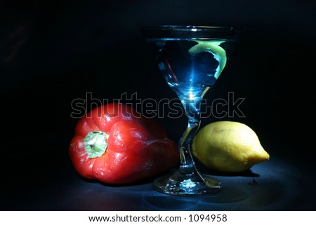 about 2 seconds time laps (on each item indvidually) aka bulb exposure still life of a martini with lemon twist a red bell pepper with green stem and yellow lemon on black light up with light