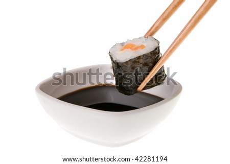 About to put delicious makizushi in soy sauce. Isolated on white