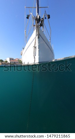 Above and below underwater sea level photo of sail boat docked in open ocean sea #1479211865
