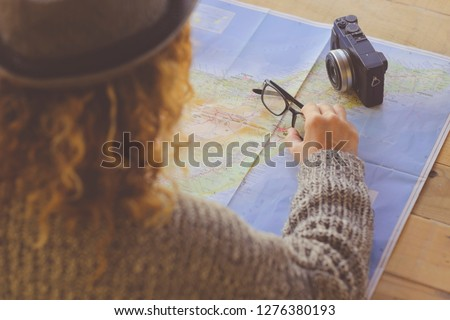 Above and rear view curly woman planning next travel vacation on a paper map - eyeglasses and digital vintage camera on the table - wanderlust and dreamer people 2019 trend