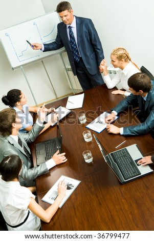 Above angle of business people listening to confident man during seminar